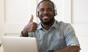 African guy in headphones sitting near computer smiling looking at camera showing thumbs up, online audio educational course advertisement, teacher and student successful distant communication concept